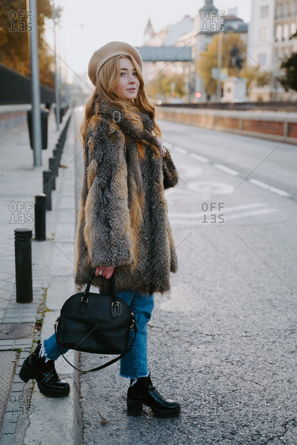 Side view of young female in trendy warm coat and beret crossing road during stroll in city and looking away