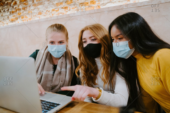 Group of multiethnic female freelancers in masks working on laptop in cafe while discussing new business project during coronavirus epidemic