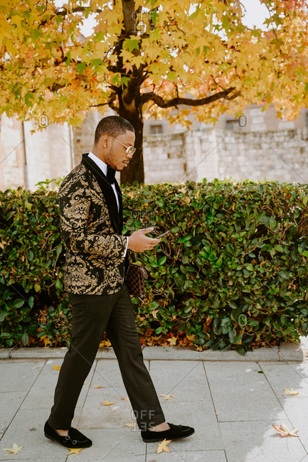 Side view of rich African American male in posh tuxedo standing in street while browsing on smartphone looking away