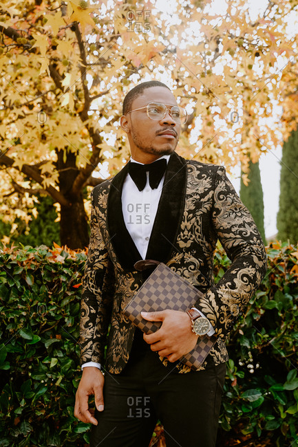 Elegant African American male wearing expensive tuxedo walking along street and looking away