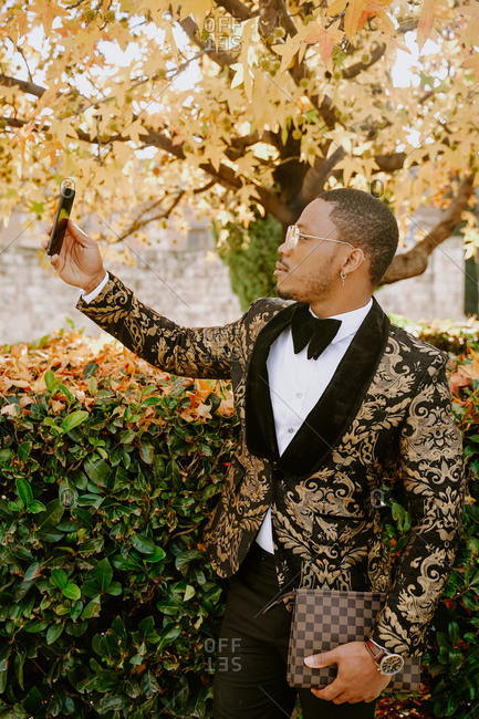 Side view of rich African American male in posh tuxedo standing in street and taking photo on selfie camera of smartphone