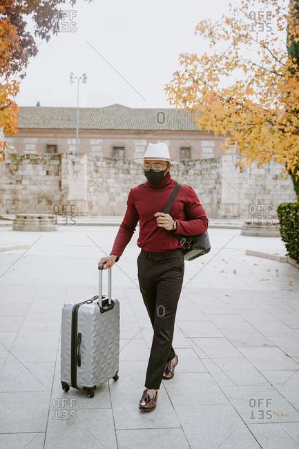 Elegant African American male traveler wearing protective mask walking along street with suitcase after flight during coronavirus