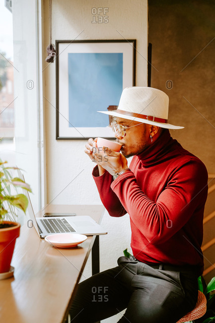 Side view of trendy African American male entrepreneur sitting in cafe and enjoying fresh coffee during break at remote work