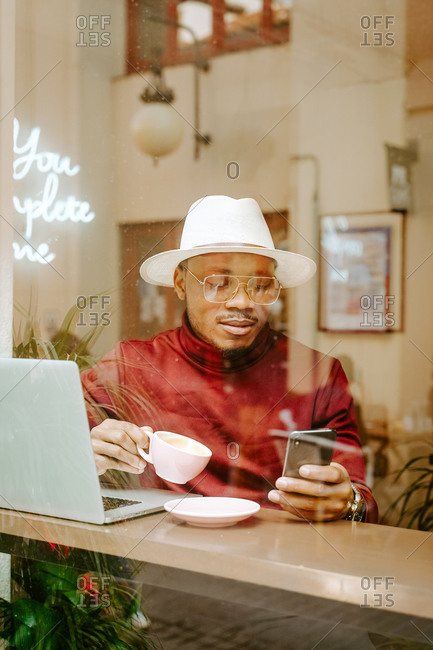 Stylish African American male in hat sitting at table in coffee shop and browsing smartphone while enjoying fresh hot drink and chilling at weekend