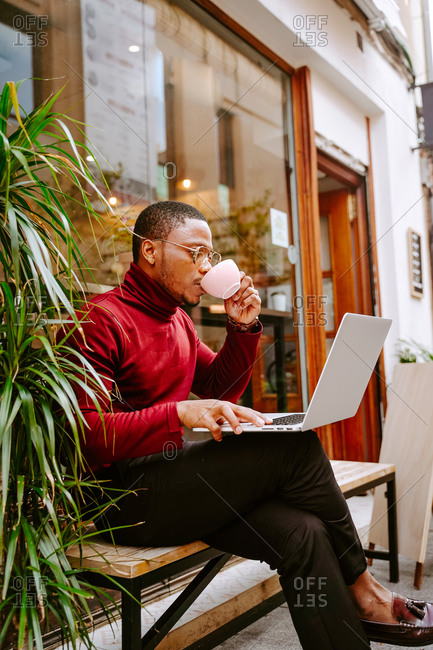 Side view of rich stylish African American male entrepreneur sitting on bench near cafe outdoors and browsing laptop while drinking delicious coffee and working remotely on project