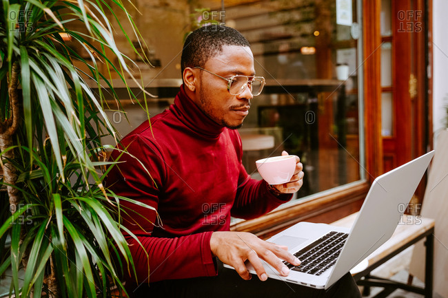 Side view of rich stylish focused African American male entrepreneur sitting on bench near cafe outdoors and browsing laptop while drinking delicious coffee and working remotely on project
