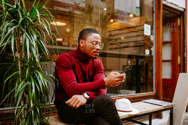 Stylish African American male sitting on bench near coffee shop and surfing internet on mobile phone on street