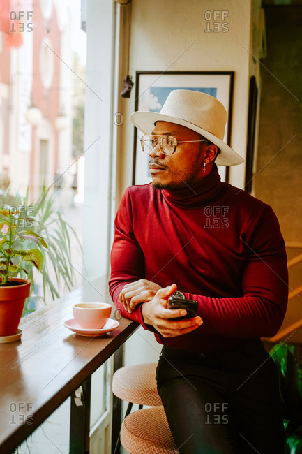 Pensive African American male in stylish outfit sitting at counter in coffee shop while chilling at weekend and looking out of window