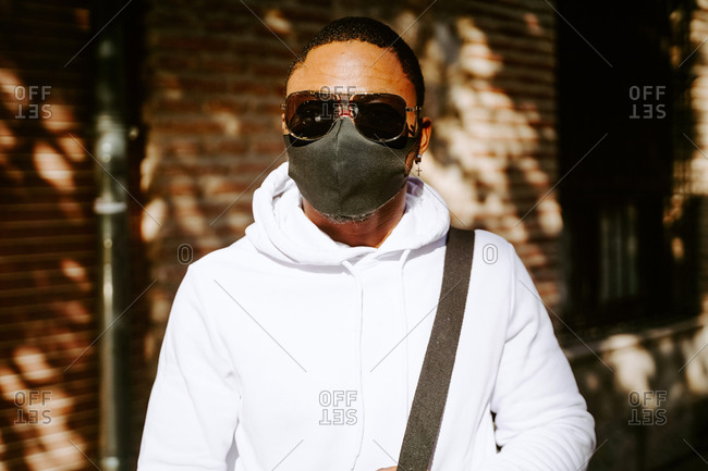 Stylish African American male in sunglasses and protective mask standing on street during coronavirus epidemic