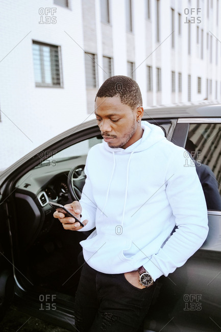 African American male standing near expensive car and surfing Internet on smartphone