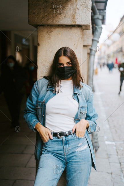 Confident young female in trendy denim clothes and black protective mask for coronavirus prevention looking at camera while standing near stone column on city street
