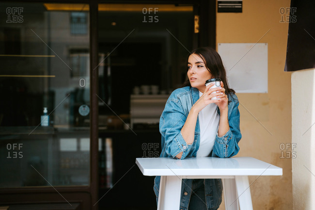 Relaxed young female in denim outfit drinking takeaway coffee while resting at table on cafe terrace