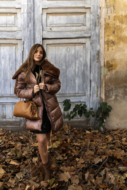 Fashionable young smiling ethnic female with long dark hair in stylish outfit and hat standing in autumn park near aged house with shabby walls and wooden door looking at camera