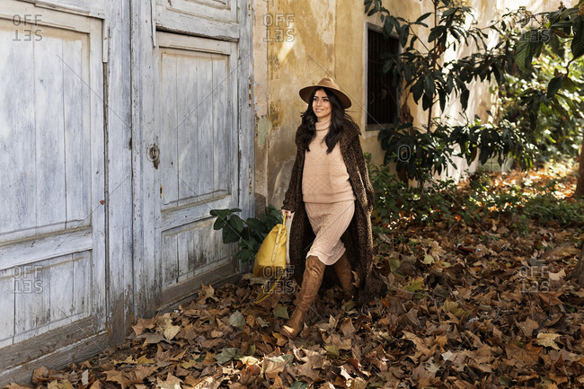 Full length of fashionable young smiling ethnic female with long dark hair in stylish outfit and hat walking in autumn park near aged house with shabby walls and wooden door