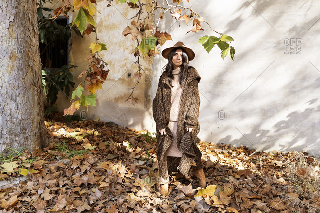 Fashionable young smiling ethnic female with long dark hair in stylish warm winter outfit and hat standing in autumn park near aged house with shabby walls looking at camera