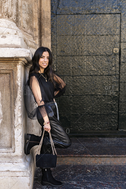 Side view of self esteem young ethnic female in total black trendy outfit standing near entrance of aged medieval building with hand on waist and looking at camera