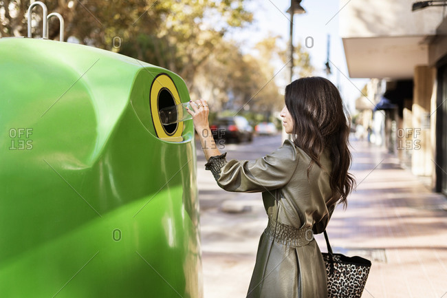 Side view of young stylish ethnic female in leather dress throwing plastic bottle into green recycling bin placed on city street