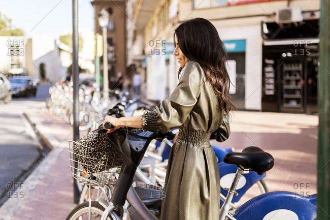 Side view of young content ethnic female with long dark hair in fashionable outfit smiling while renting bicycle at sharing system standing on city street