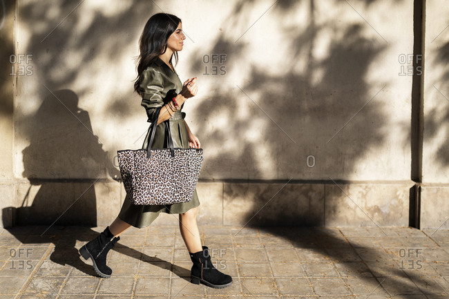 Side view of positive young ethnic female pedestrian with long dark hair and handbag in trendy leather dress walking along paved street near white wall on sunny day