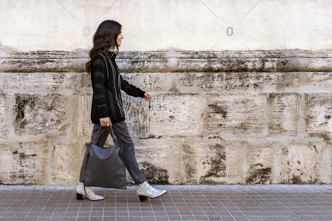 Side view of positive young female pedestrian with long dark hair and handbag in trendy clothes walking along paved street near white wall on sunny day