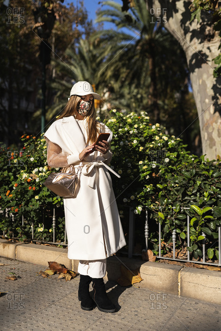 Young stylish female in protective mask standing on street on sunny day and messaging on social media via mobile phone