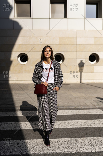 Delighted female in trendy outfit crossing roadway on sunny day in city and looking at camera