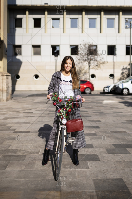 Full body of happy young female in stylish casual wear riding bicycle decorated with flowers on paved square in city looking at camera