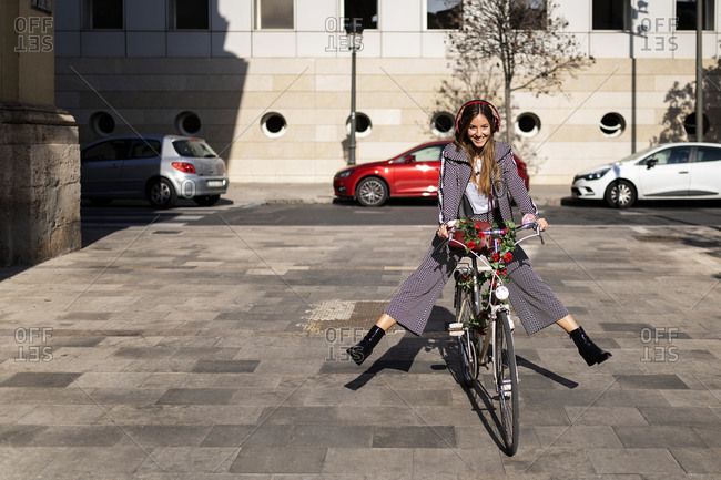 Full body of happy young female in stylish casual wear and headphones having fun while riding bicycle decorated with flowers on paved square in city