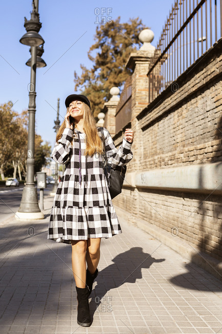 Full body of cheerful young female in stylish checkered coat and hat talking on mobile phone while walking along city street in sunny autumn day