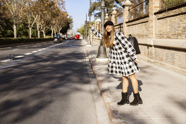 Full body of stylish young female traveler in trendy checkered coat standing on sidewalk and catching taxi in sunny autumn city