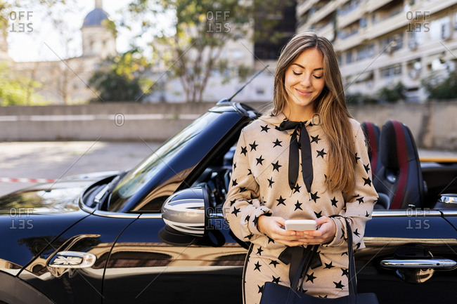 Positive young female in stylish outfit using mobile phone while leaning against convertible luxury automobile on city street