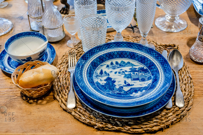 From above of blue ceramic plates served on wooden table with elegant glassware and silverware
