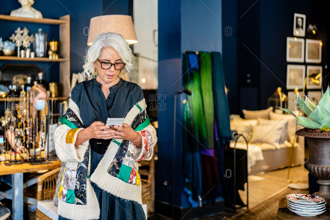 Elegant middle aged female in stylish outfit and glasses messaging on mobile phone while spending time at home with vintage interior
