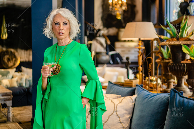 Mature female wearing green elegant dress standing with glass of alcohol drink in luxury house and looking at camera