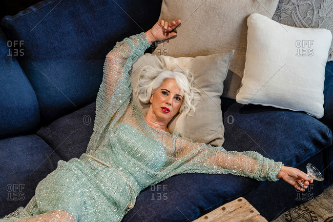 From above of mature female in glamour dress with glitter lying on couch with cocktail glass and relaxing after party in luxury house while looking at camera