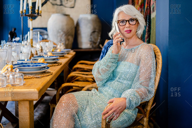Charming middle aged female in expensive glittering dress sitting on chair in luxury dining room and speaking on mobile phone while looking at camera