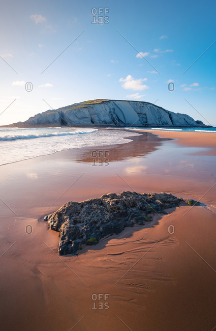 Picturesque scenery of chalk cliff located on amazing Playa de Covachos sandy beach washing by foamy sea from both sides against sunset sky in Cantabria