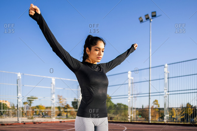 Focused fit female standing on sports ground while warming up and stretching raised arms before active calisthenics workout