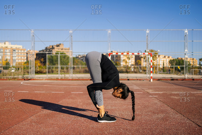 Side view of flexible female doing forward bend and stretching legs while warming up before calisthenics workout on sports ground