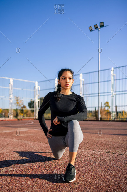Concentrated female athlete doing lunge exercise and stretching legs while warming up during calisthenics training