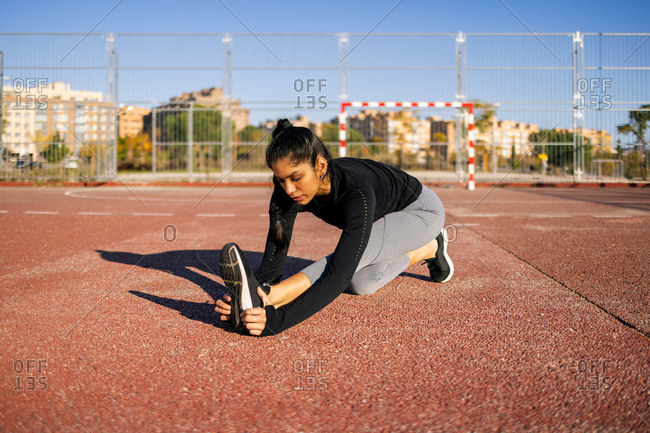 Concentrated female athlete doing stretching exercise while warming up during calisthenics training