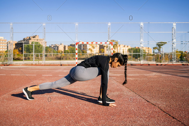 Side view of concentrated female athlete doing lunge exercise and stretching legs while warming up during calisthenics training