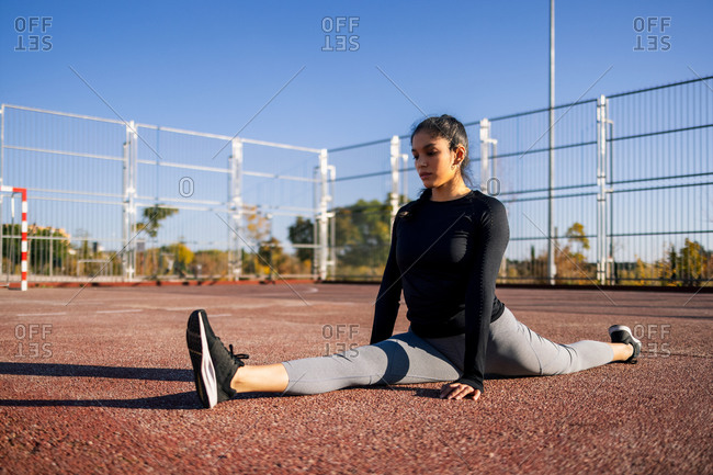 Slender flexible female sitting on sports ground and performing splits while stretching legs during calisthenics training