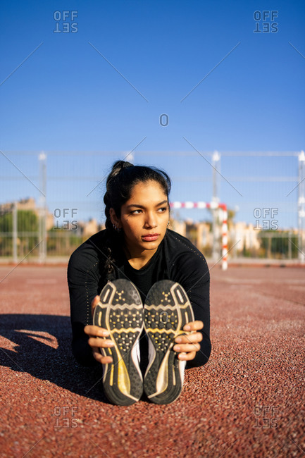 Serious flexible ethnic female athlete sitting on sports ground and stretching legs while doing forward bend exercise during calisthenics training and looking away