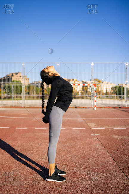 Side view of flexible slender female doing backbend while standing on sports ground in summer and stretching body during calisthenics workout