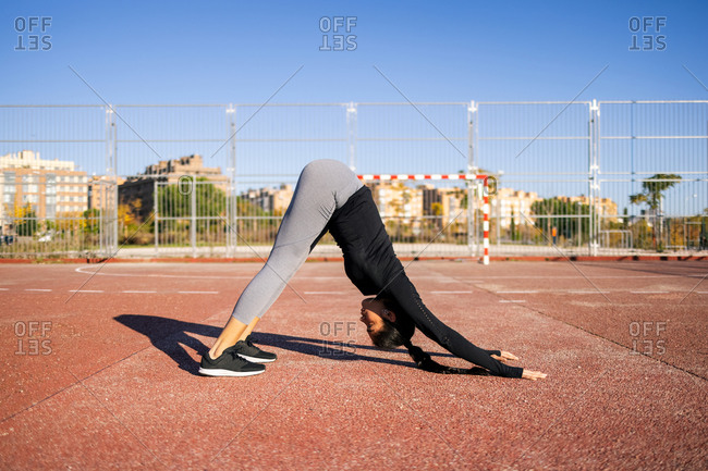 Side view of slim flexible female athlete performing downward facing dog pose while doing yoga on sport ground