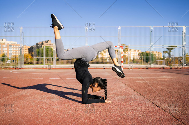 Side view of slim flexible female athlete performing splits while balancing in handstand during calisthenics training