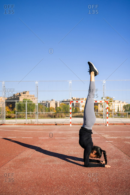 Side view of slender female in sportswear balancing in handstand while doing exercises during calisthenics training