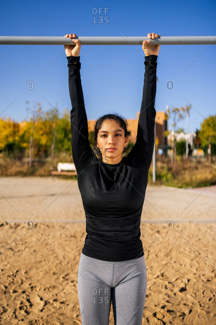 Determined ethnic female athlete hanging from horizontal bar during calisthenics training and looking at camera