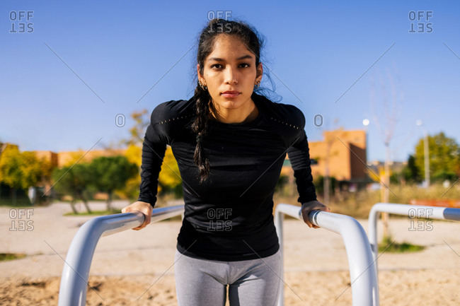 Confident slim ethnic female doing triceps exercise on parallel bars during calisthenics workout and looking at camera